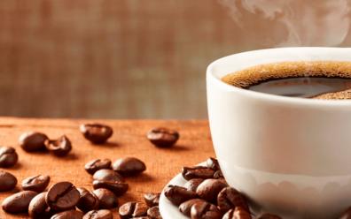 xícara com café dentro e grãos de café espalhados ao lado