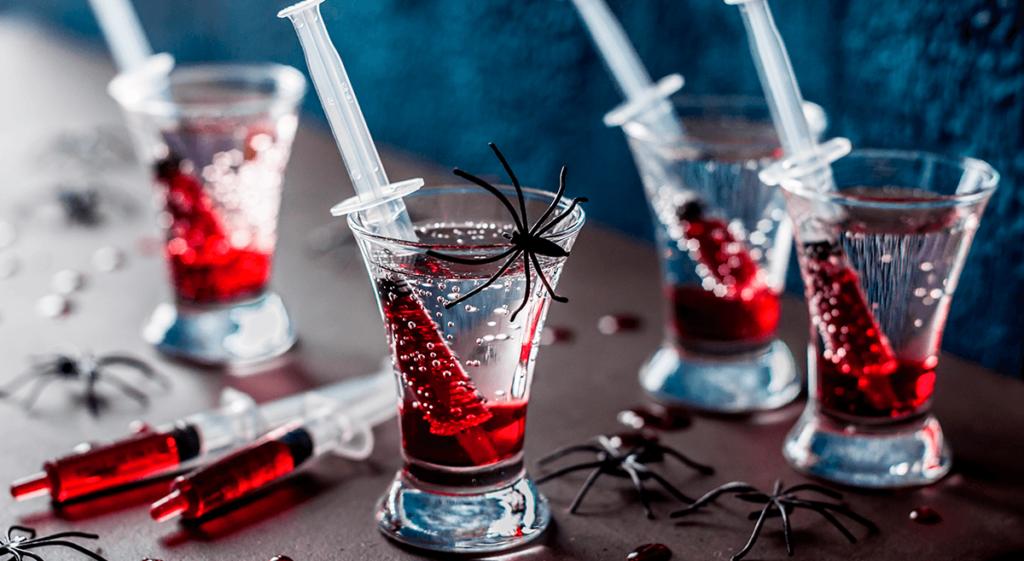 copo-pequeno-com-bebida-e-seringa-de-platico-e-corante-vermelho