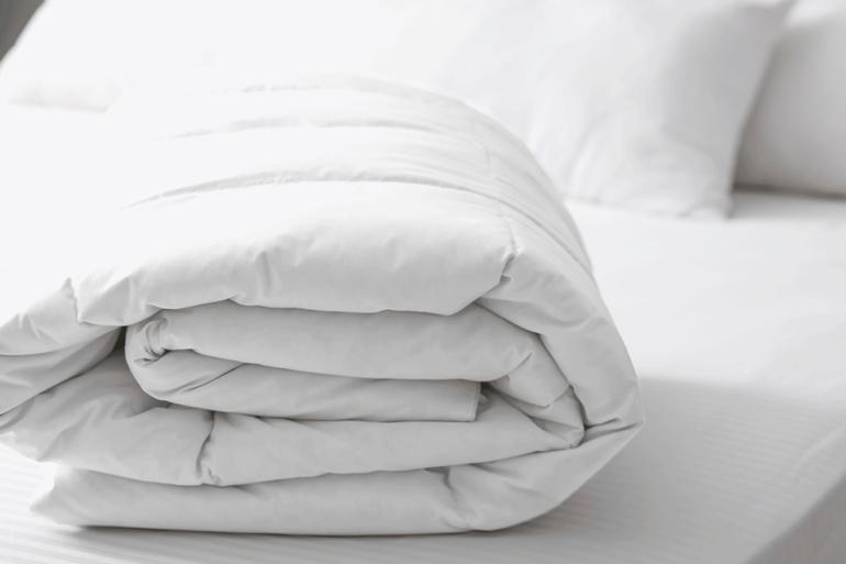 edredom casal 100% algodão dobrado em cima de uma cama