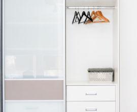guarda-roupa de porta de correr aberto com espelho e cabides