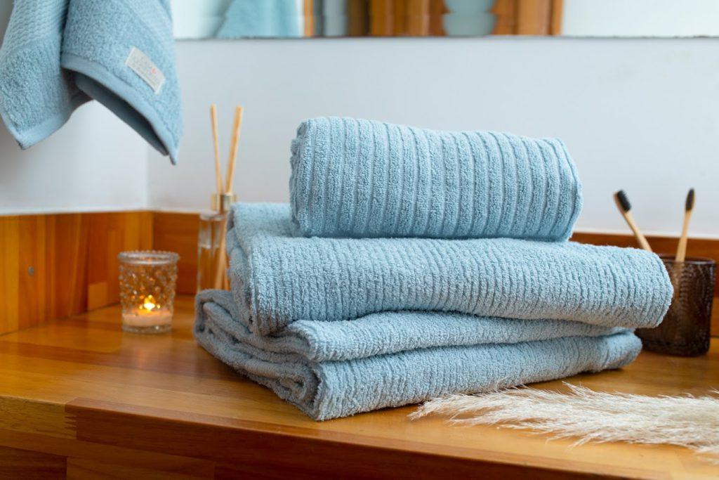 jogo-de-toalha-de-banho-azul-claro-em-cima-da-bancada