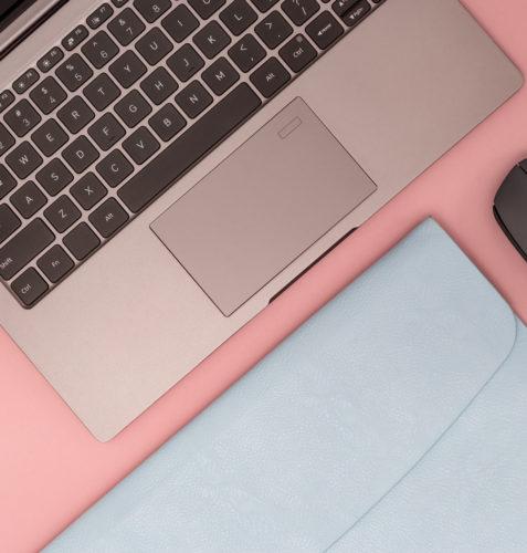 mesa rosa com notebook, mouse e capa para notebook azul