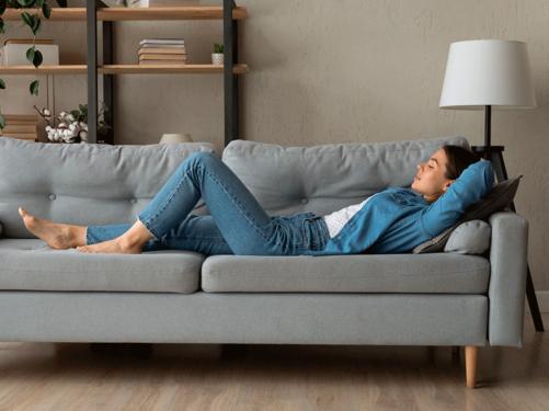 mulher deitada em um sofá confortável