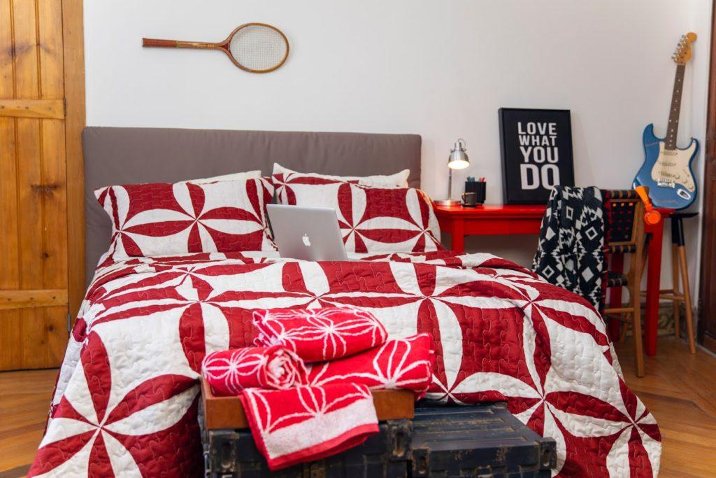 Um jogo de cama vermelho e branco aparece como destaque em um quarto arrumado
