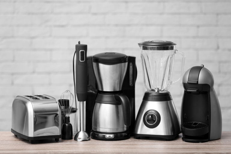 Itens de casa lado a lado, sobre uma mesa: liquidificador, cafeteira, sanduicheira, mixer