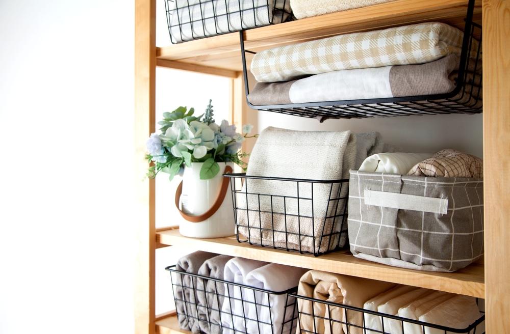 Uma estante com caixas e cestos organizadores com toalhas e outras peças de roupas